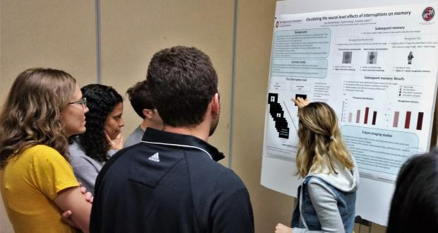 Student presenting her research poster to attendees
